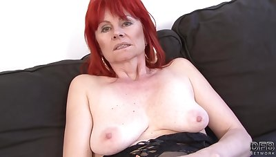 Red haired granny in dispirited lingerie is having casual sex with a black guy, on the sofa